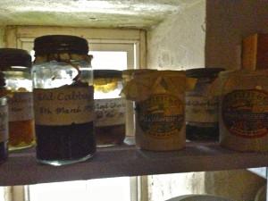 A 1928 Larder; jars of preserves, jellies, jams; ceramic jars of vinegars, flour, sago, onions and vegetables